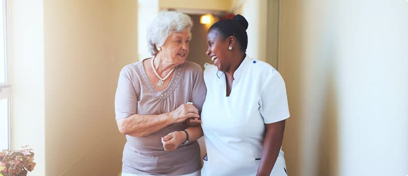 elderly woman and a caregiver talking