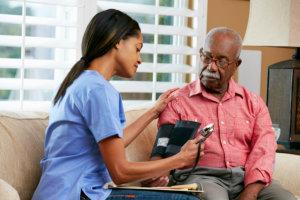 a nurse and an elderly man at home